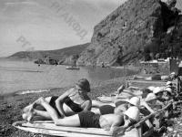 Пионеры, отдыхающие в лагере «Артек», загорают на пляже.