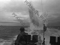Катер-охотник атакует глубинными бомбами вражескую подводную лодку. Северный флот, 1941 г. РГАКФД. Арх. № 0-255566.